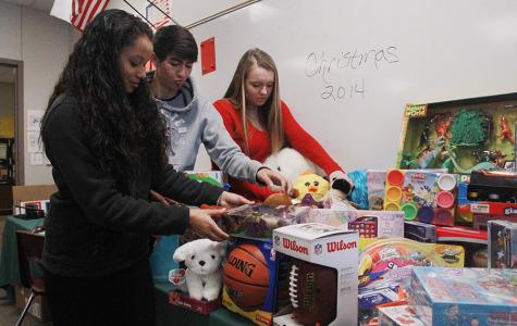 Students Raza Mahmoud, Justin Oviedo and Cassidy Morgan work together to give presents to children that otherwise wouldn't have any