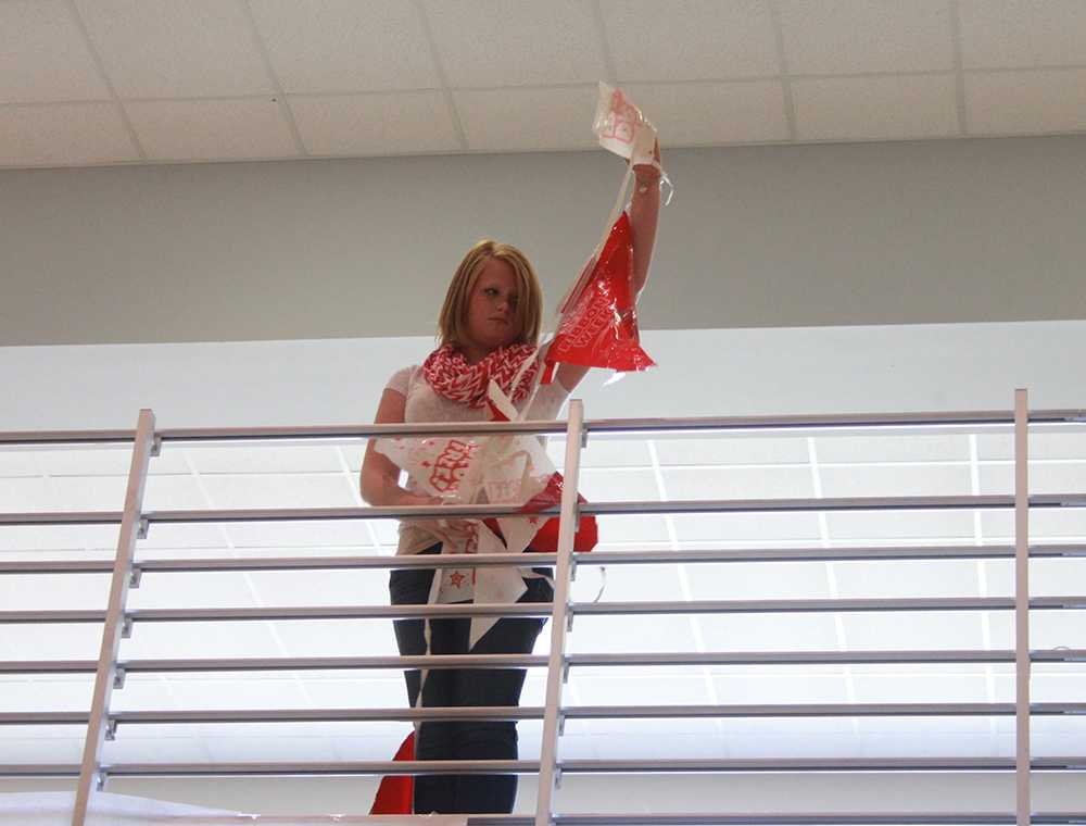 Above the Commons, freshman Hannah Jones hangs decorations for Red Ribbon Week.