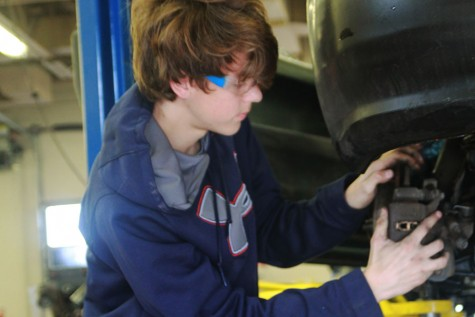 Senior Wesley Blake changes a tire in Auto Tech.
