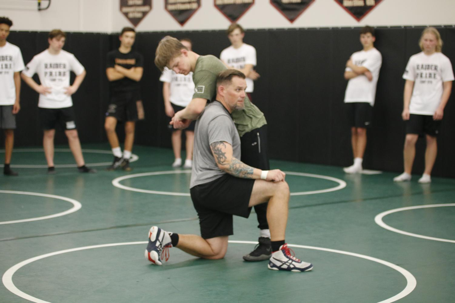 READY TO RUMBLE  Senior Thomas Tolbert and new wrestling coach Lehi Benton demonstrate a fundamental move for team members during an after-school practice.
