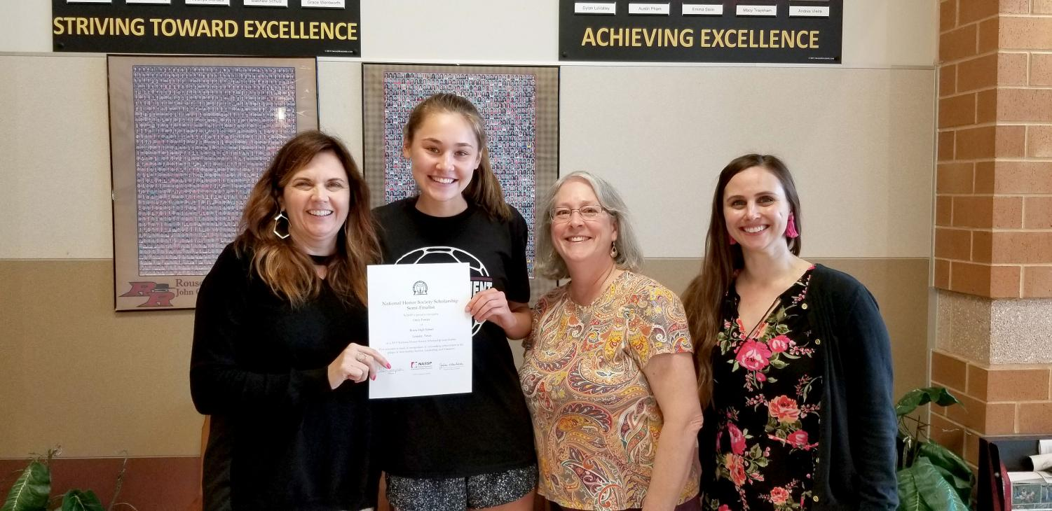 Principal Christine Simpson presents senior Emily Forster with her NHS scholarship, while sponsors Marguerite Swilling and Megan Pilewski show their support.