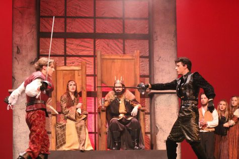 Queen Gertrude 12, King Claudius 11, watch intensely as Laertes 12 and Hamlet 11 duel.