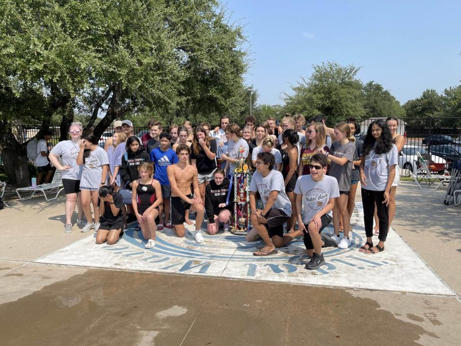 The swim team poses with their trophy after winnning their first meet against Glenn and Leander.