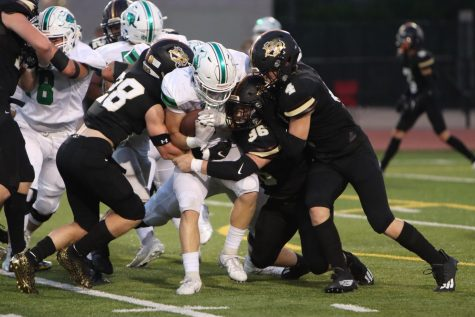 Working together, senior defenders Ashton Davis and Christian Lyons work to take down the ball carrier.